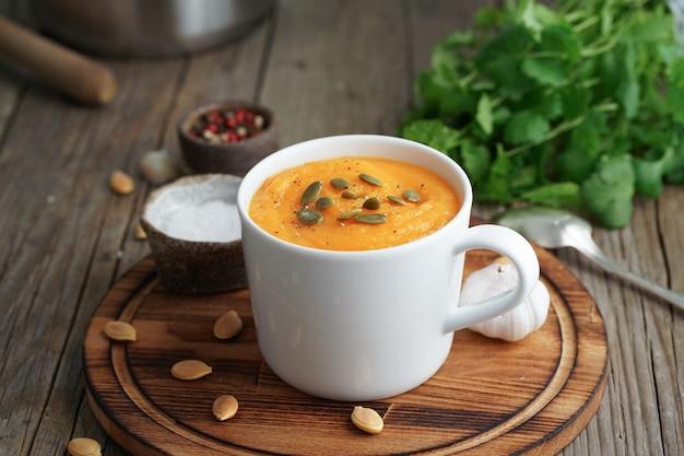 Puré de creme da sopa da abóbora no copo na tabela de madeira marrom, vista lateral.
