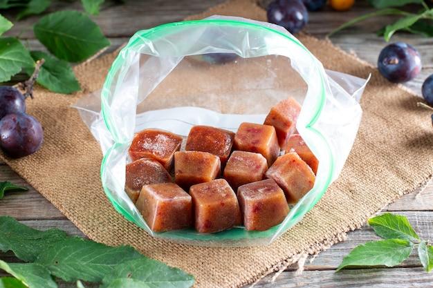 Purê de frutas congeladas em cubos de gelo em cima da mesa. ameixa congelada, ameixa cereja. armazenamento de alimentos