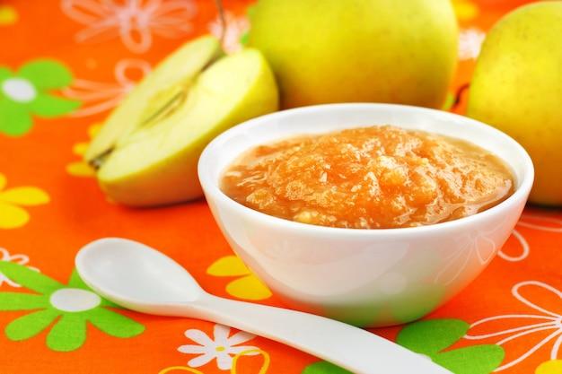 Purê de maçã caseiro em uma tigela na toalha de mesa colorida