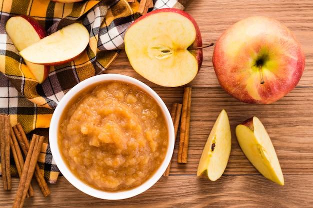Purê de maçã, maçãs e canela em uma mesa de madeira, vista superior