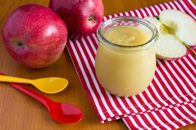 Purê de maçã na jarra e maçã vermelha no guardanapo