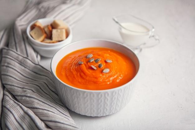 Purê de sopa de abóbora com creme e sementes em um fundo branco.