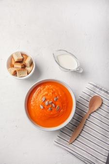 Purê de sopa de abóbora com pão ralado, creme e sementes em um fundo branco. copie o espaço.