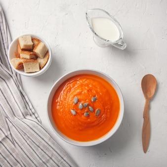 Purê de sopa de abóbora com pão ralado, creme e sementes em um fundo branco.