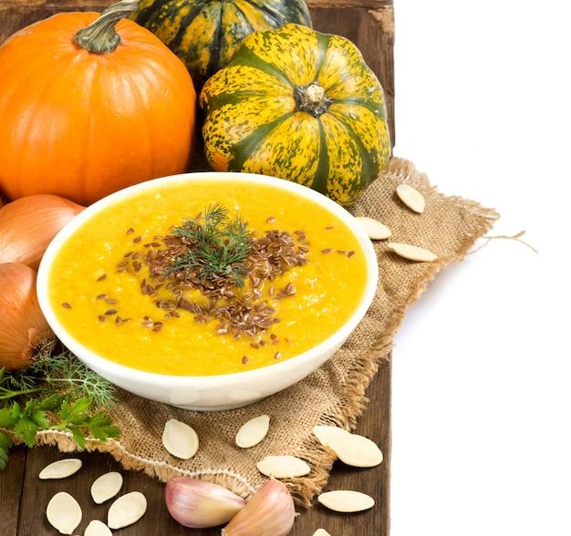 Purê de sopa de abóbora fresca em uma tigela e pampkins crus em uma mesa de madeira fechar
