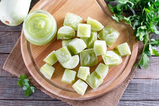 Purê de vegetais congelados na mesa de madeira. cubos de purê de abobrinha congelados. conceito de alimentos congelados.