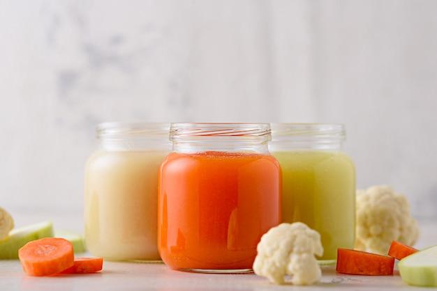 Purê de vegetais infantis de cenoura, abobrinha, couve-flor em potes de vidro branco