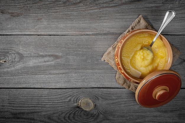 Pure or desi ghee também conhecido como manteiga líquida clarificada. pure or desi ghee em tigelas de cerâmica sobre uma velha mesa de madeira. vista do topo.