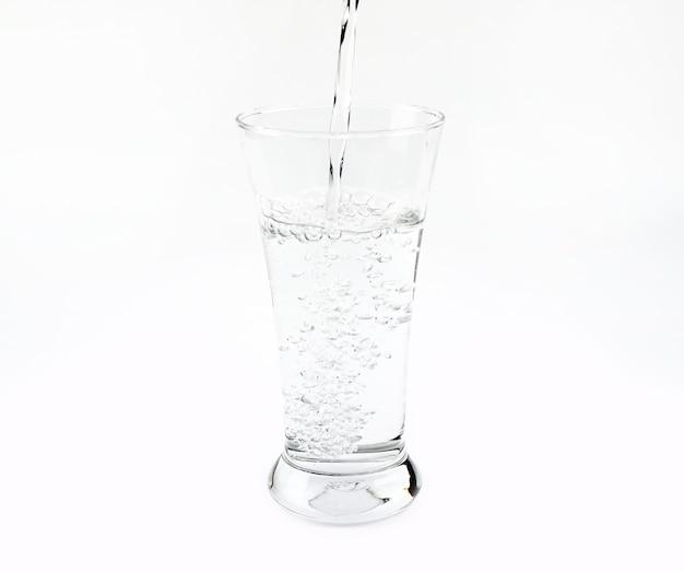 Purgar água em vidro isolado no fundo branco Foto Premium