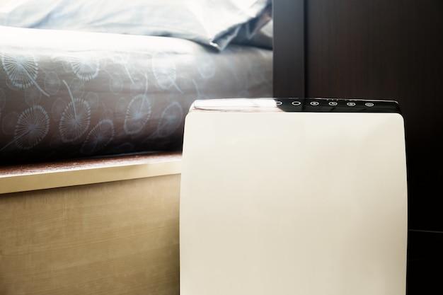 Purificador de ar no limpador de quarto de cama removendo poeira fina em casa.