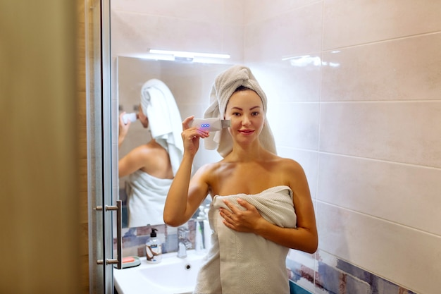 Purificador ultrassônico para limpeza da pele do rosto. a garota no banheiro cuida do rosto dela.