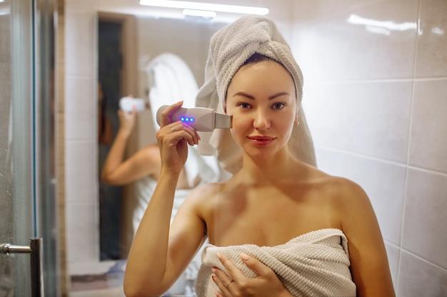 Purificador ultrassônico para limpeza de pele facial garota no banheiro cuida de seu rosto