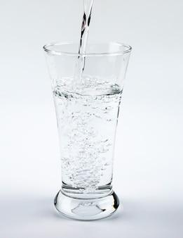 Purificando água em vidro no fundo branco