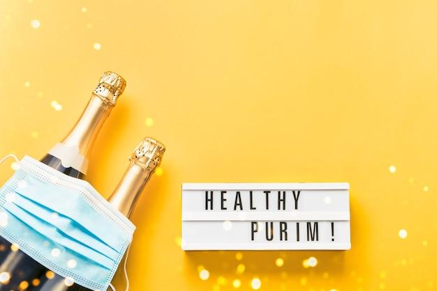 Purim saudável escrito em lightbox, duas garrafas de champanhe e máscara médica em um amarelo