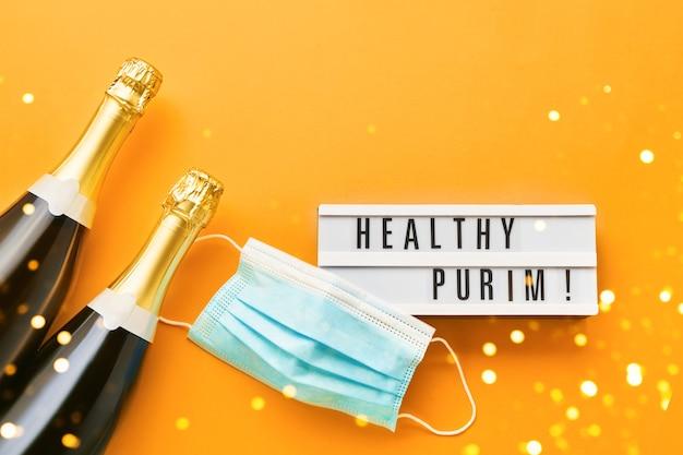 Purim saudável, escrito em lightbox, duas garrafas de champanhe e máscara médica em uma laranja. postura plana do conceito de celebração do carnaval de purim.