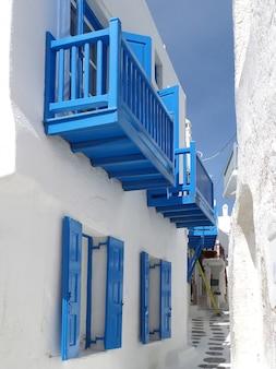 Puro branco e vivas casas azuis e um pequeno beco na cidade de mykonos, ilha de mykonos da grécia