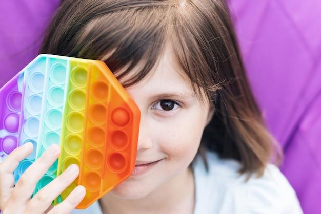 Push pop it e simples covinha nas mãos das crianças, feche o retrato da menina com um brinquedo moderno popit