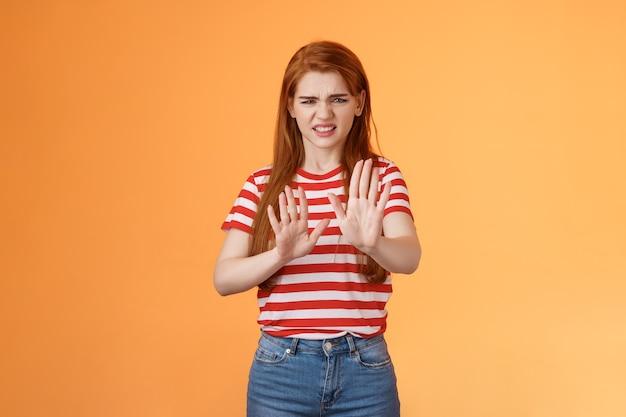 Puxa, fede, ruiva enojada, mulher exigente, bloqueando o sinal, levante as mãos defensiva fazendo careta ...