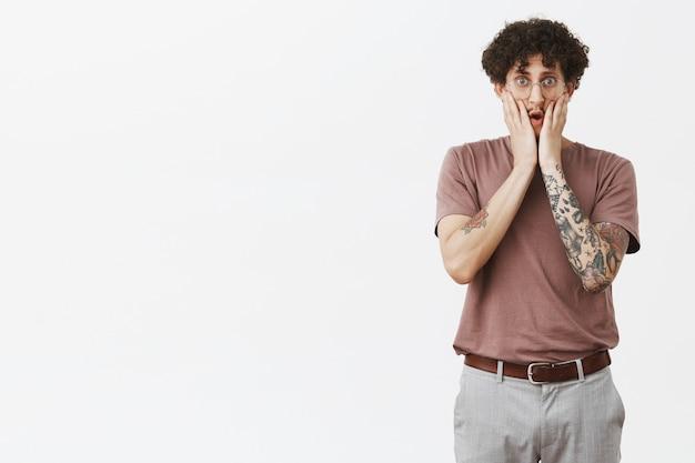 Puxa, isso é chocante. retrato de um jovem urbano bonito e atordoado com um braço tatuado e bigode em óculos, de mãos dadas no rosto, expressando empatia e preocupação com a parede cinza