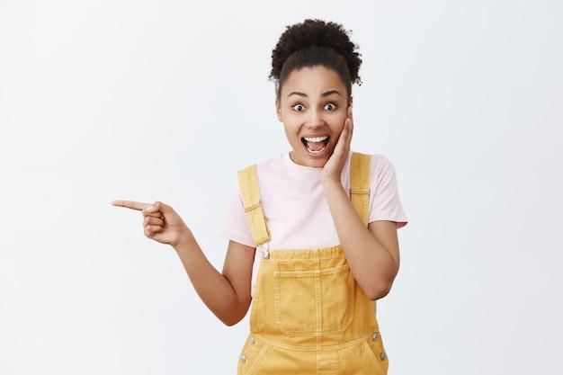 Puxa, que ótima notícia. retrato de uma mulher bonita surpresa e surpresa em um macacão amarelo estiloso, segurando a palma da mão na bochecha, ficando encantada e impressionada, apontando para a esquerda e fazendo perguntas