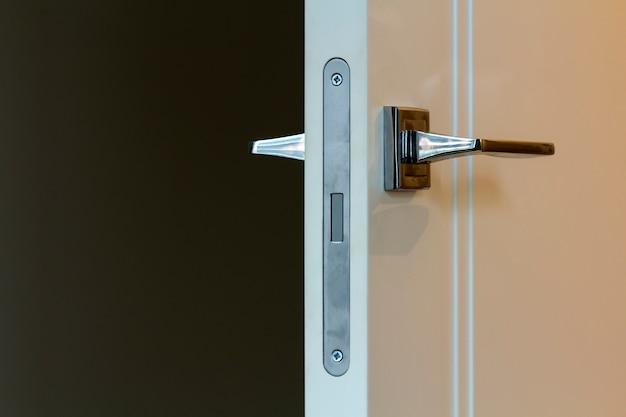 Puxador da porta de aço inoxidável moderno nas portas de madeira brancas