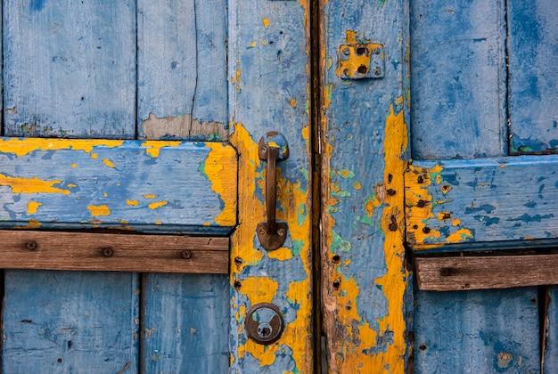 Puxadores da porta velhos e portas pintadas de azul e amarelo. superfícies antigas pintadas com óleo quase azul. textura de fundo abstrato