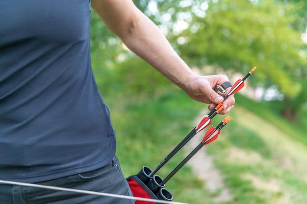 Puxando uma flecha do coldre nas corridas de arco e flecha