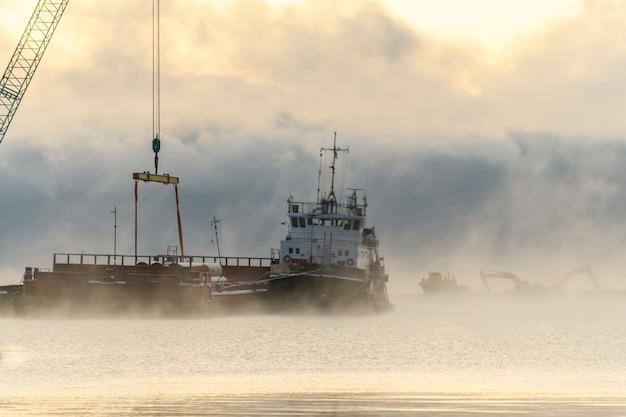 Puxão amarrado ao bardge. nevoeiro forte no mar ártico. construção obras marítimas offshore. construção de barragem, guindaste, barcaça, draga.