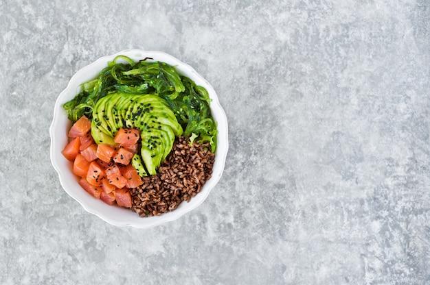 Puxar tigela. ingredientes: salmão, abacate, arroz integral, algas marinhas.