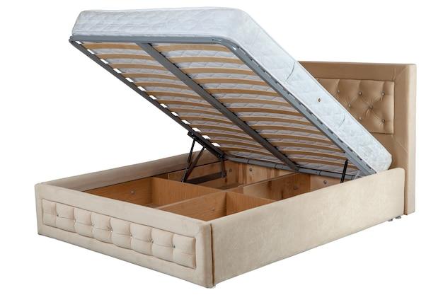 Puxe a cama de armazenamento, espaço de armazenamento revelado pela elevação da base de ripas, isolado no fundo branco, inclui traçado de recorte.