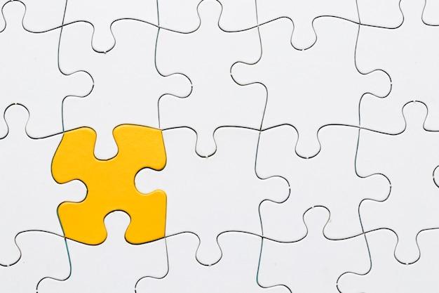 Puzzle amarelo entre grade de quebra-cabeça branca