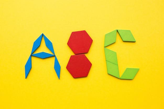 Puzzle de madeira tangram de cor em forma de letras do alfabeto abc em fundo amarelo