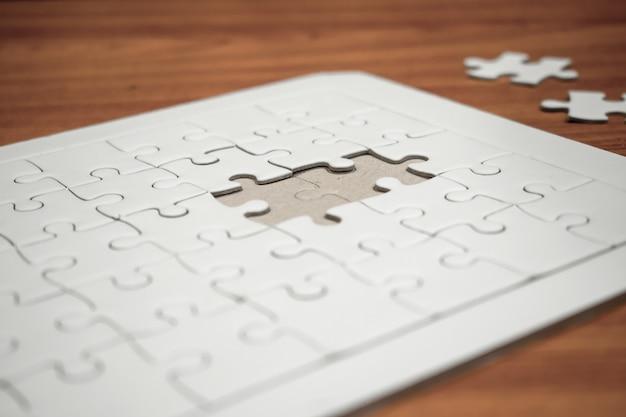 Puzzles brancos. em uma mesa de madeira marrom.