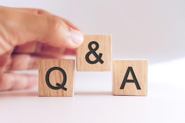 Q e a alfabeto em um cubo de madeira na mão. conceito de significado de perguntas e respostas.