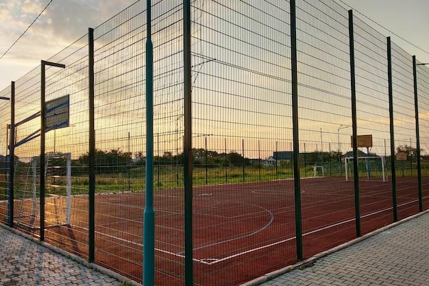 Quadra de futebol e basquete ao ar livre, cercada com cerca alta
