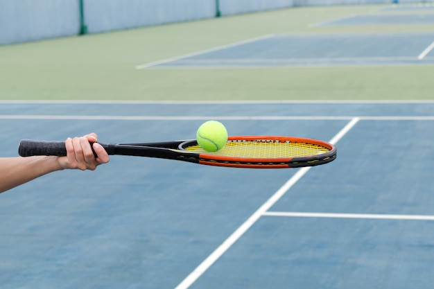 Quadra de tênis, mão segura a raquete de tênis com bola.