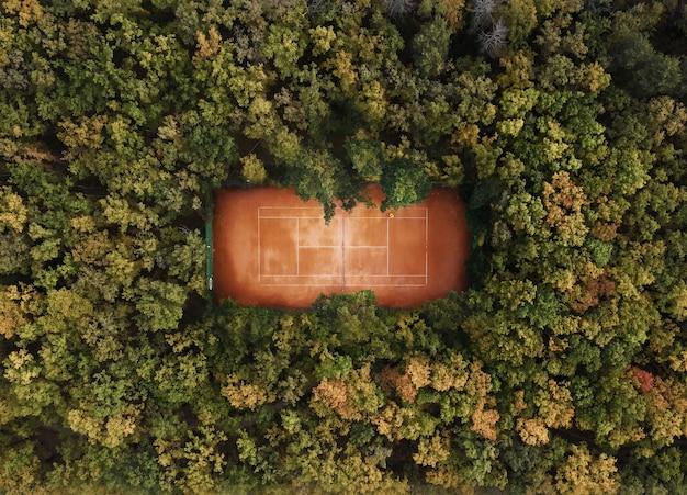 Quadra de tênis na floresta da vista aérea superior.