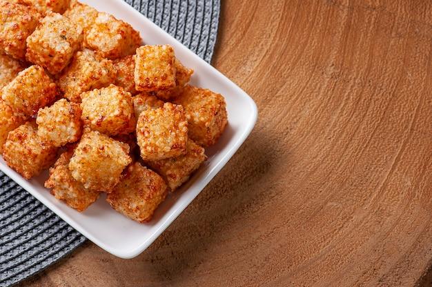 Quadrados de tapioca com queijo servidos com geleia de pimenta. mesa de madeira. espaço para texto - dado de tapioca. vista do topo. copie o espaço