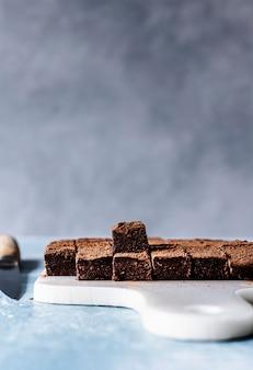 Quadrados de trufa de ganache de chocolate polvilhados com cacau em uma tábua de cortar