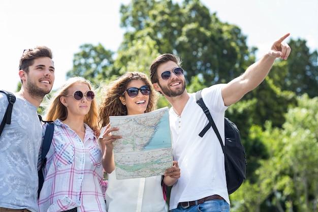 Quadril amigos segurando o mapa e apontando ao ar livre