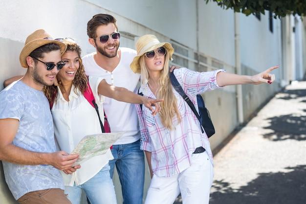 Quadril amigos segurando o mapa e apontando na cidade