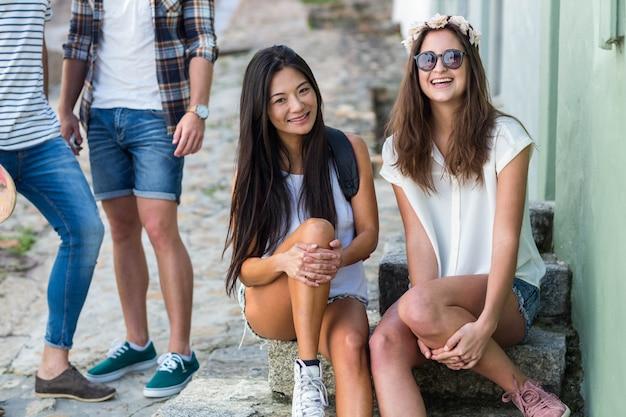 Quadril amigos sentado nos degraus da cidade e olhando para a câmera