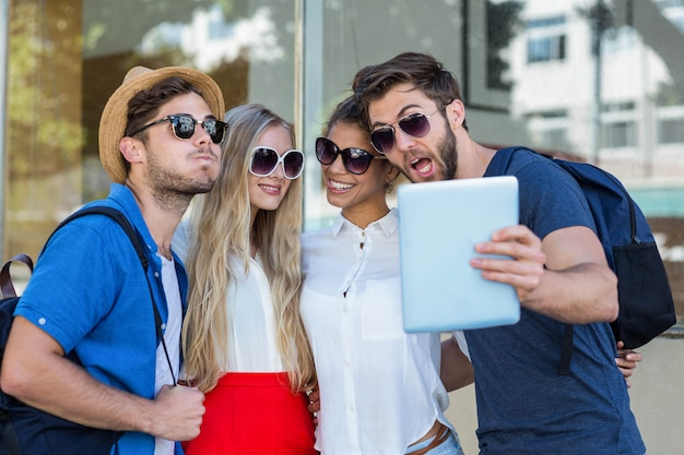 Quadril amigos tomando selfie com tablet na cidade