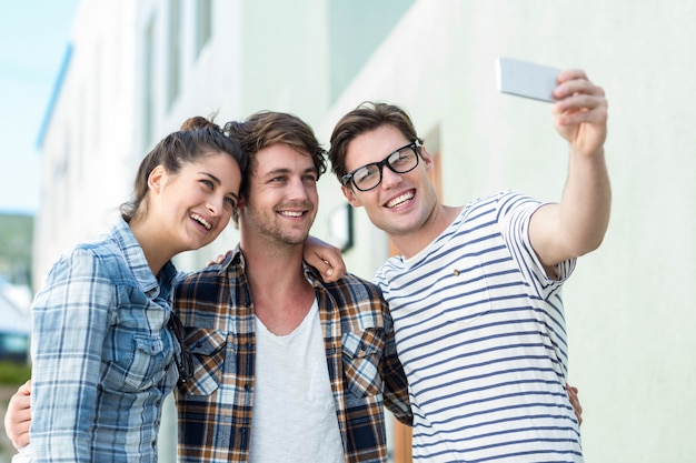 Quadril amigos tomando selfie na rua