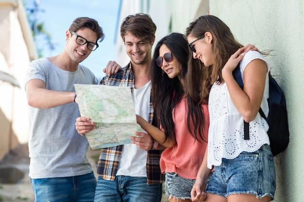 Quadril amigos verificando o mapa da cidade