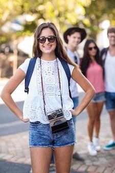 Quadril mulher sorrindo para a câmera em pé na rua