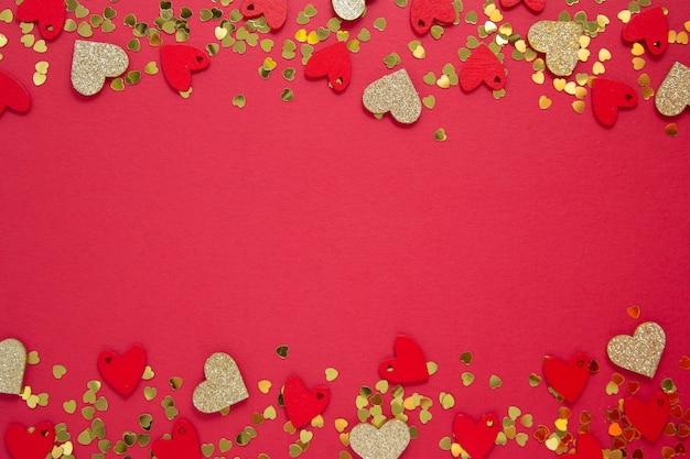 Quadro abstrato, borda, fundo vermelho com glitter dourado em forma de coração. dia dos namorados plana leigos. copie o espaço.