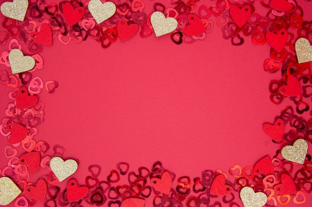 Quadro abstrato, borda, fundo vermelho com glitter dourado em forma de coração. dia dos namorados plana leigos.