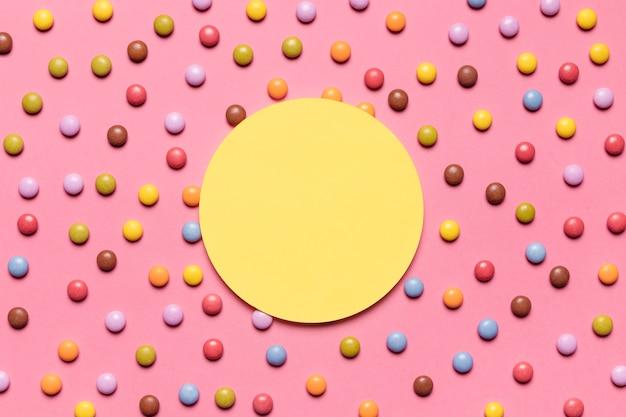 Quadro amarelo circular sobre os doces coloridos gema multicoloridos em fundo rosa