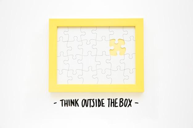 Quadro amarelo com peça de quebra-cabeça faltando perto pensar fora do texto da caixa
